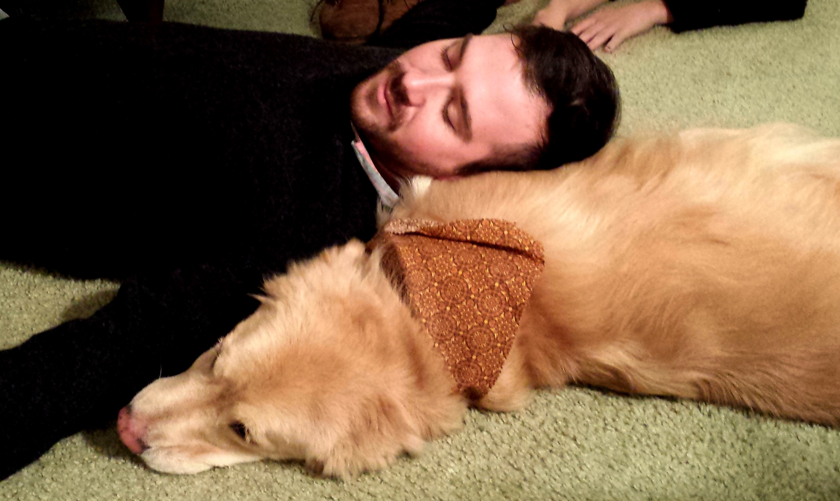 Young man has head resting on golden retriever's shoulder
