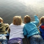 Kids enjoy sunny day lying on dock