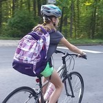 Girl with backpack cycles to school