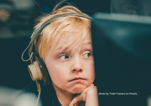 School child in headphones next to computer monitor