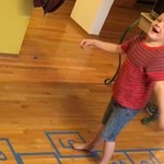 CHild plays indoor hopscotch