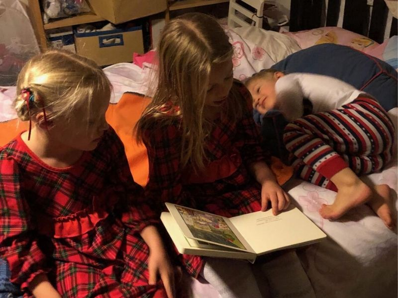 Girl reads book to two younger siblings