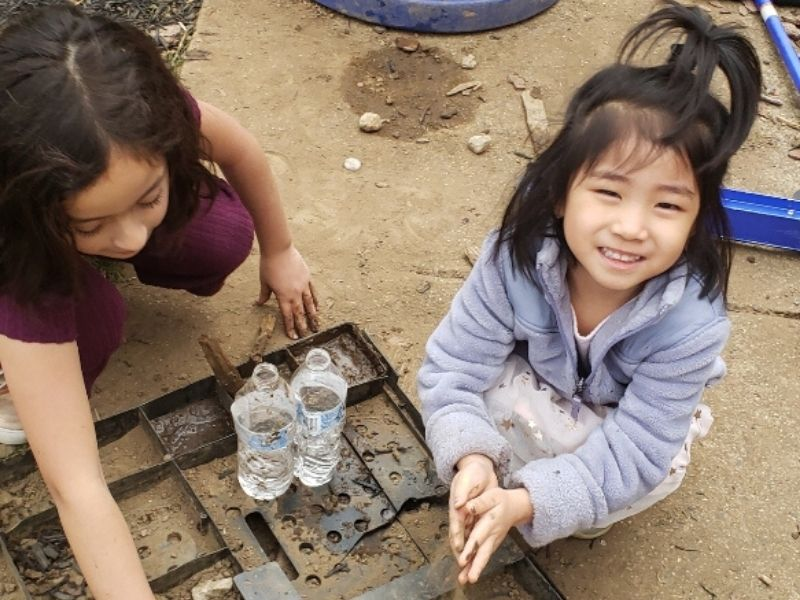 Little girl smiles as she plays in mud with her sister