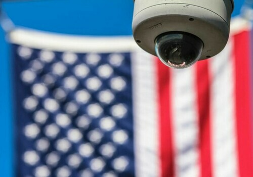 A surveillance camera appears in front of an American flagmerican flag