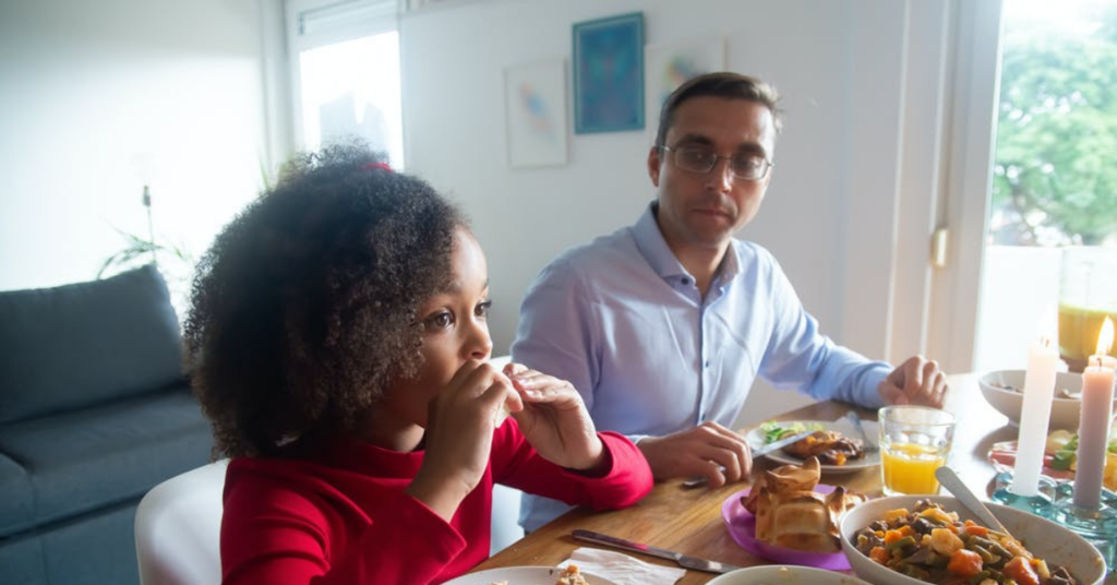 Father looks at child as both have dinner