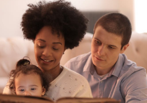 Woman, Man and Little Child read a Book