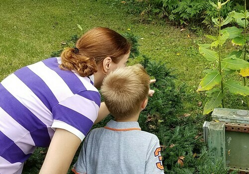 Mom and child in park look at plants
