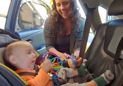 Shannon at car door and Cooper in carseat get ready for a trip