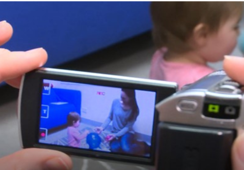 Photo of hands on a video camera trained at a child and mother playing on the floor. Photo courtesy Australia Infant Communication and Engagement Study